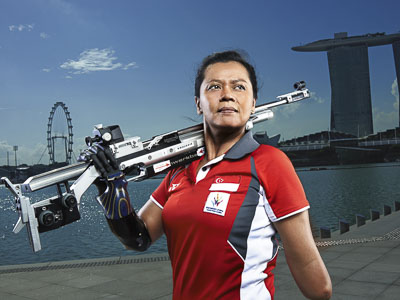 woman sports portrait holding air rifle with no hand in front of singapore Marina bay sands | Tuckys Photography